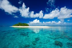 Beautiful tropical island paradise with white sand, tall palm trees, fluffy white clouds, a dark blue sky and surrounded by turquiose water and coral reef